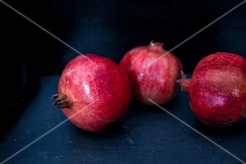 Three pomegranates on a blue wooden table