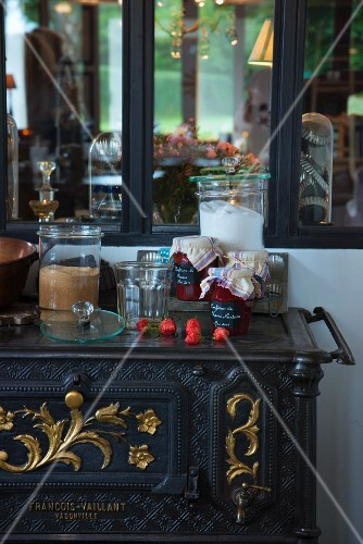 Jam jars and fresh strawberries on top of antique cooker