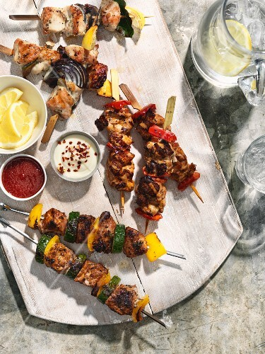 Various grilled skewers with vegetables and dips