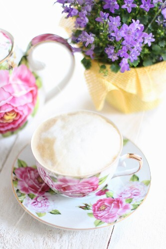 A cappuccino in a rose-patterned cup