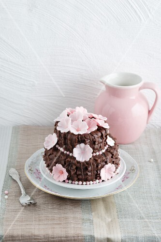 A chocolate cake decorated with chocolate butter cream ruffles with cherry jam and sugar cherry blossom