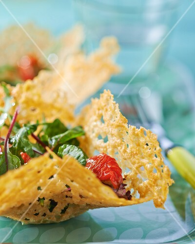 A mixed leaf salad with tomato confit in a Parmesan basket