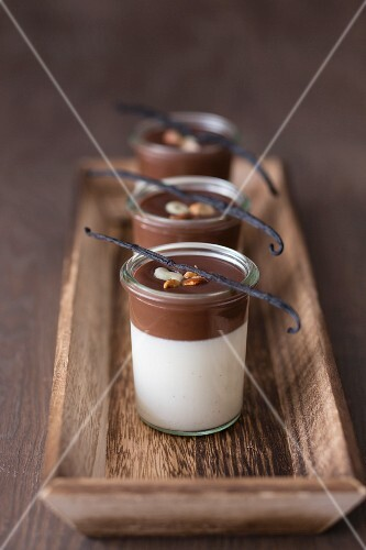 Vanilla panna cotta with chocolate sauce, garnished with roasted almonds, chocolate raisins and vanilla pods