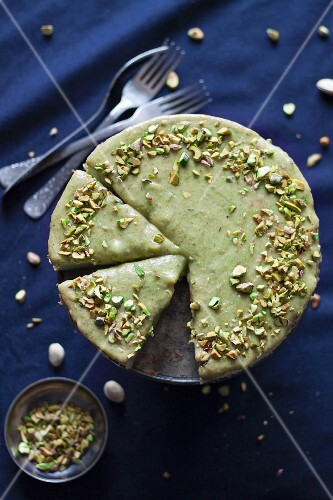 Pistachio cheesecake with a pistachio glaze and chopped pistachios, sliced (seen from above)