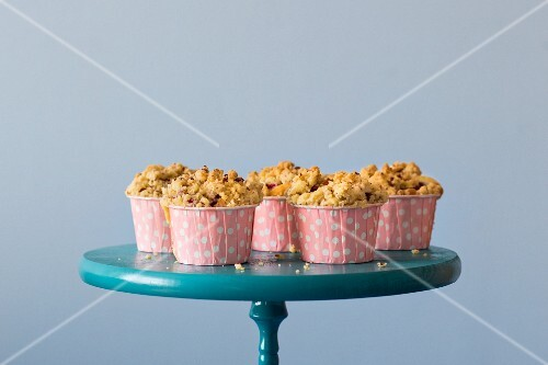 Raspberry crumble muffins in pink polka dot case on a blue cake stand