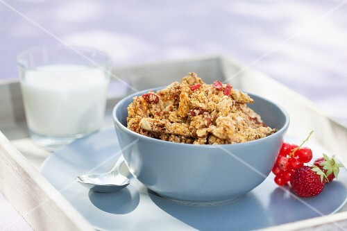 A bowl of muesli on a tray with fruit and a glass of almond milk next to it