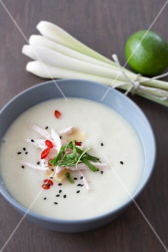 Coconut soup with chicken strips, bamboo shoots, coriander and black sesame seed with a bundle of lemongrass and a lime next to it