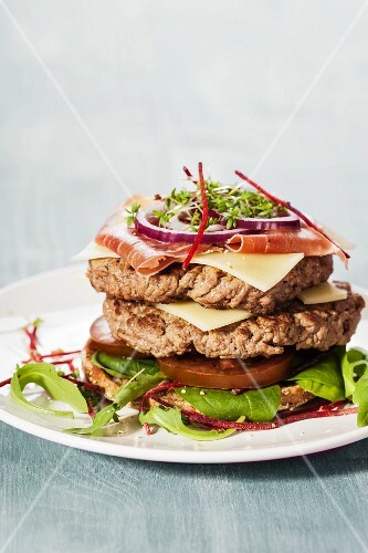 An bun-less double hamburger with ham, cheese, black tomatoes, red onion and cress