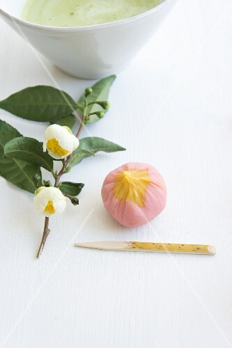 Wagashi plum (ume) next to a flowering sprig of tea leaves and a bowl of matcha tea