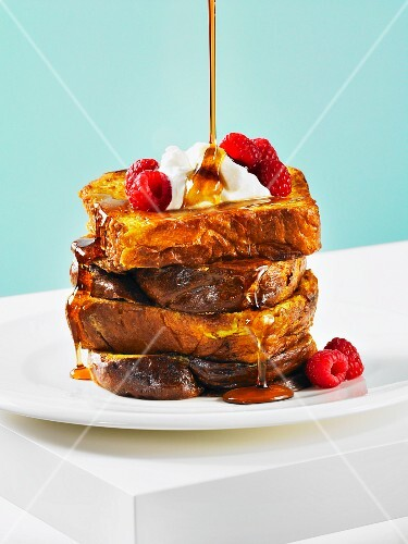 French toast with maple syrup, whipped cream and raspberries