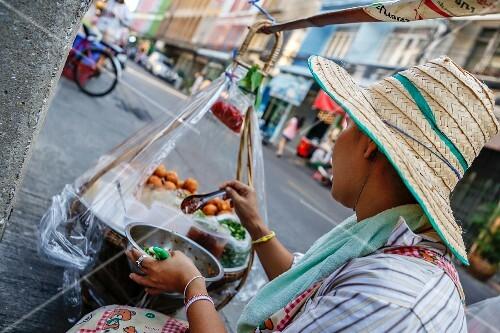 A mobile street seller preparing food in a street kitchen (Bangkok, Thailand)