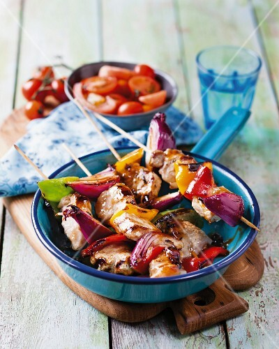 Pork skewers with peppers, onions and tomato salad