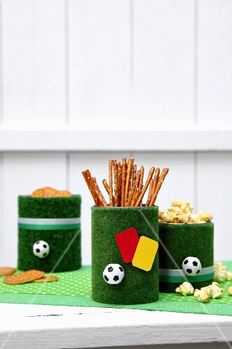 Snack in old tin cans covered with artificial grass decorated with mini footballs and yellow and red referees' cards