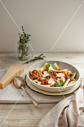 Pasta with beef ragout, Parmesan cheese and basil