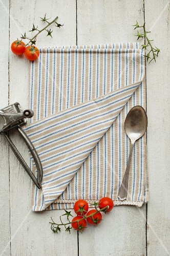 A kitchen towel, a spoon, cherry tomatoes and a cheese grater