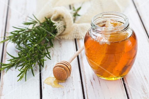 A jar of honey with a honeycomb with fresh rosemary next to it