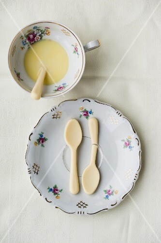 White chocolate spoons on a plate and a cup of hot white chocolate