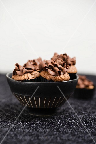 Mini chocolate cupcakes with a chocolate ganache topping in bowl