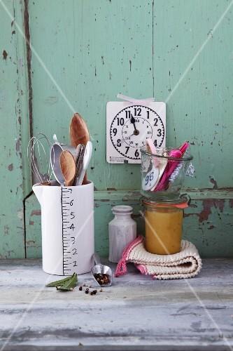 An arrangement of kitchen utensils for stirring, a clock and a preserving jar