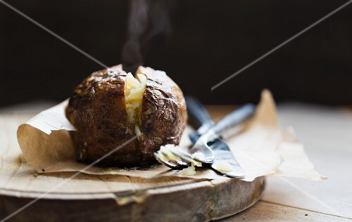 A steaming baked potato on a piece of baking paper