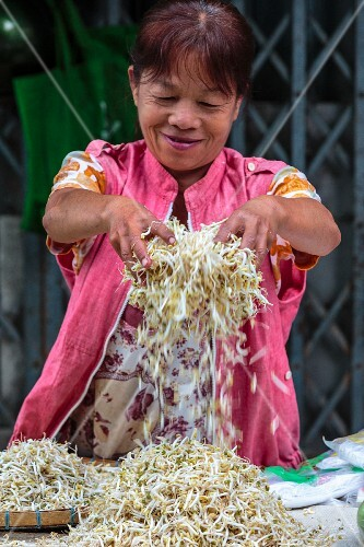A woman selling bean sprouts at a market in Thailand