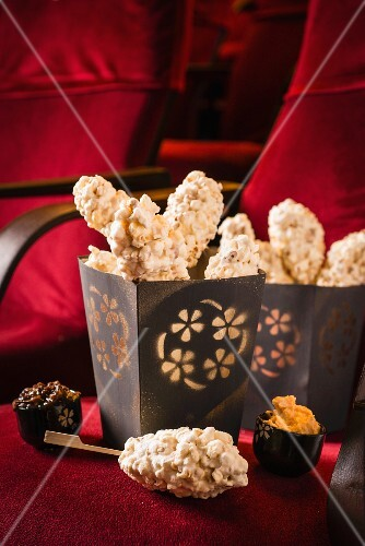 Chocolate and marshmallow popcorn skewers in a bag on a cinema seat