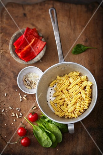 Cooked fusilli in a colander with ingredients for pepper sauce