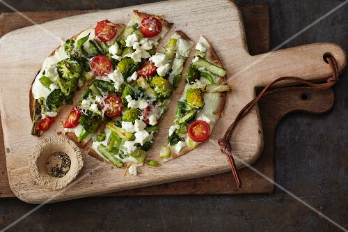 Vegetarian tortilla pizza with green asparagus, broccoli and tomatoes