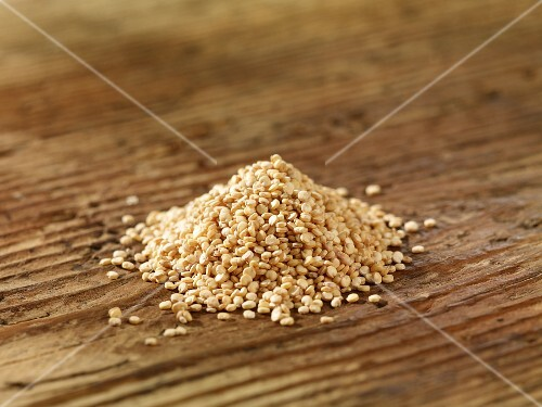 A pile of quinoa on a wooden surface