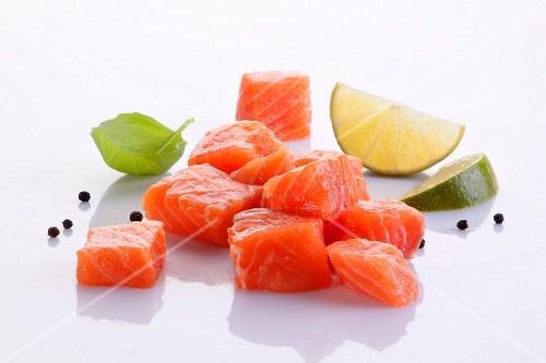Diced fresh salmon, a basil leaf, peppercorns and lime wedges