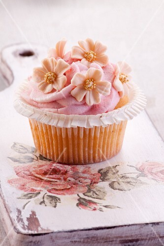 A cupcake with strawberry mousse and sugar flowers