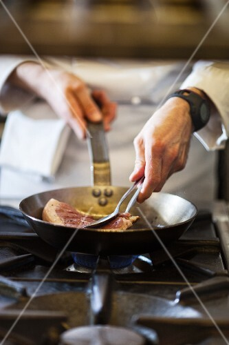 A chef preparing a steak in a commercial kitchen