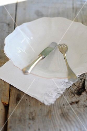A white plate and cutlery with a napkin on a wooden table