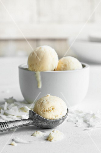 A bowl of coconut ice cream and an ice cream scoop with coconut shaving in between