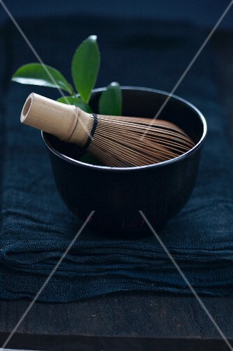 A matcha whisk and tea leaves in a tea bowl