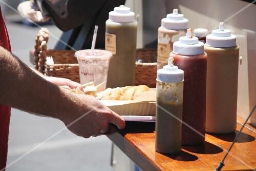 A burger and various salsas at a food truck festival in California, USA