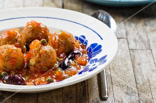 Vegan tofu balls in tomato sauce with capers and black olives
