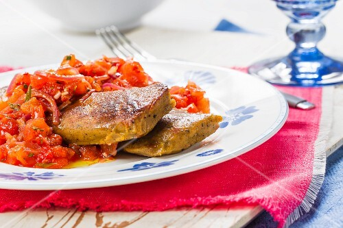 Fried wolf fish fillets with a spicy tomato sauce