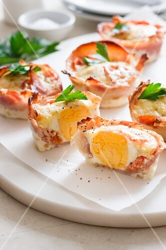 Baked eggs wrapped in bacon, whole and halved