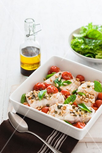 Baked fish fillets with tomatoes, basil, capers and pine nuts