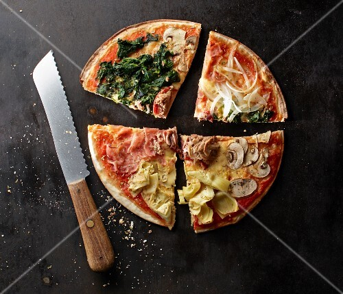 A pizza with spinach, mushrooms, artichokes, Parma ham, onions and tuna fish, sliced