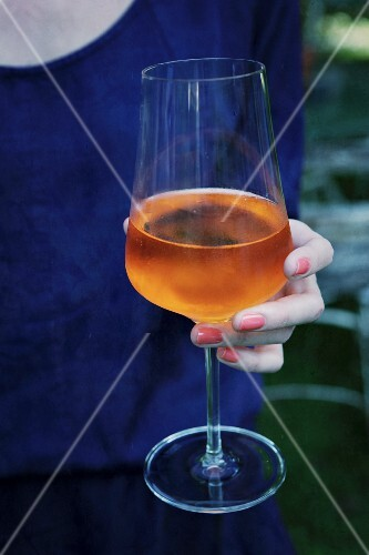 A woman holding a glass of Aperol Sprizz