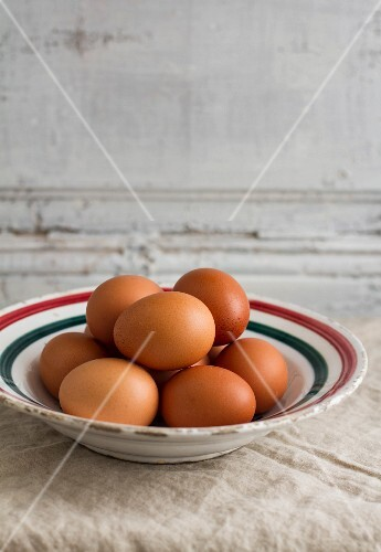 Fresh brown eggs on a ceramic plate