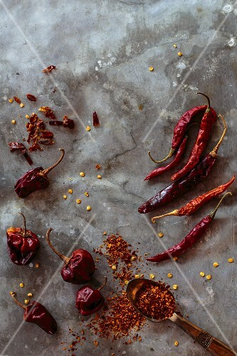 Various dried chilli peppers and chilli flakes (seen from above)
