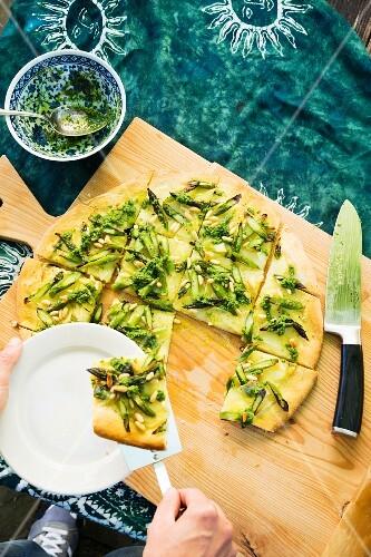 Vegan potato and asparagus pizza served with wild garlic sauce