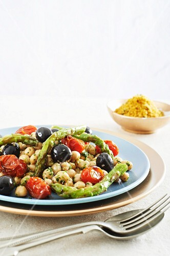 A warm vegetable salad with chickpeas, green asparagus and cherry tomatoes served with lemon breadcrumbs