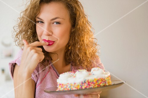 A young woman tasting a birthday cake
