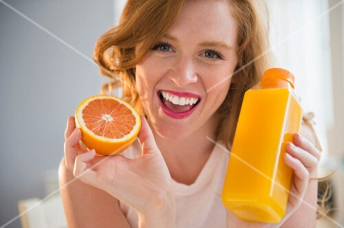 A woman holding an orange and a bottle of orange juice