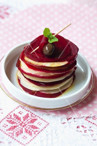 A stack of apple and beetroot slices with balsamic vinegar and mint