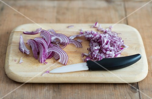 Red onions, sliced with a knife on a chopping board